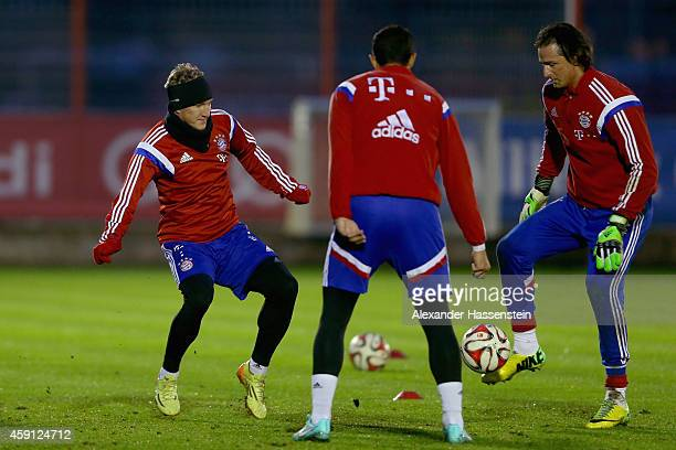 Bastian Schweinsteiger of Bayern Muenchen battles for the ball with his team mates Heinz Mueller and Medhi Benatia during a training session at...