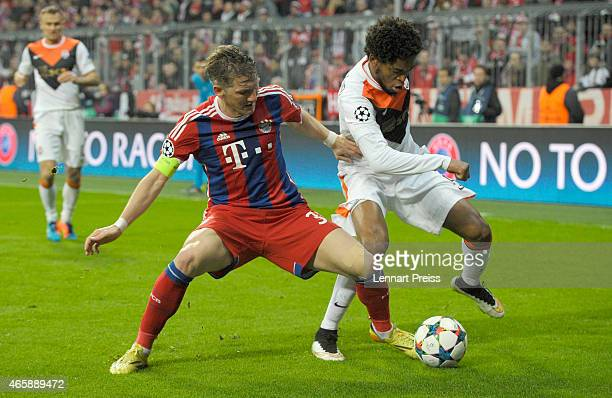 Bastian Schweinsteiger of Bayern Muenchen challenges Luiz Adriano of Shakhtar Donetsk during the UEFA Champions League Round of 16 second leg match...