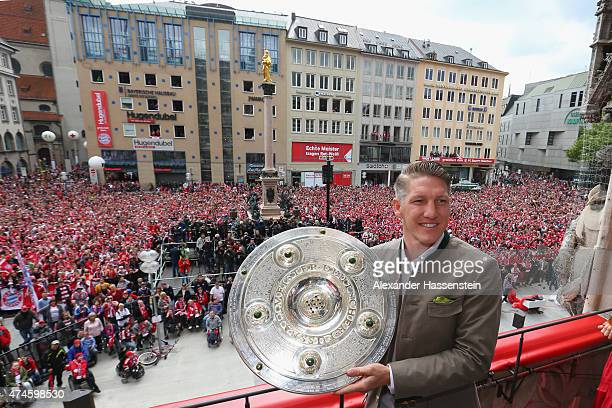 Bastian Schweinsteiger of Bayern Muenchen holds the German Championship winners trophy as the team celebrate winning the German Championship title on...