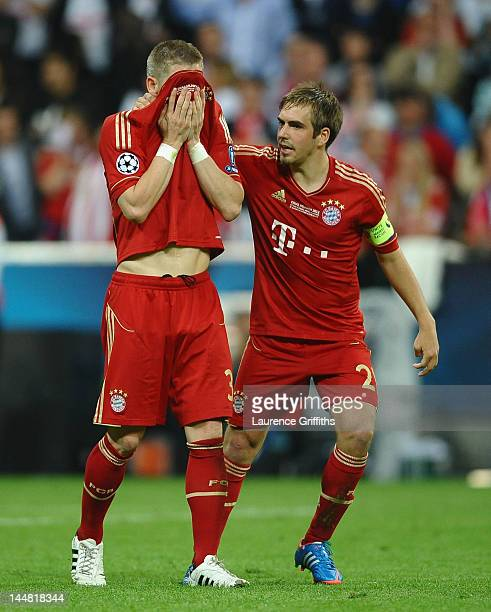 Bastian Schweinsteiger of Bayern Muenchen is comforted by Philipp Lahm after missing to score his penalty in the penalty shoot out during the UEFA...