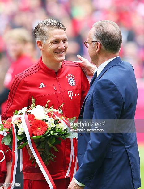 Bastian Schweinsteiger of Bayern Muenchen is congratulated by KarlHeinz Rummenigge the executive board chairman of Bayern Muenchen prior to making...