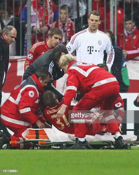 Bastian Schweinsteiger of Bayern Muenchen is laid down on a stretcher as teammates Philipp Lahm and goalkeeper Manuel Neuer watch him during the UEFA...