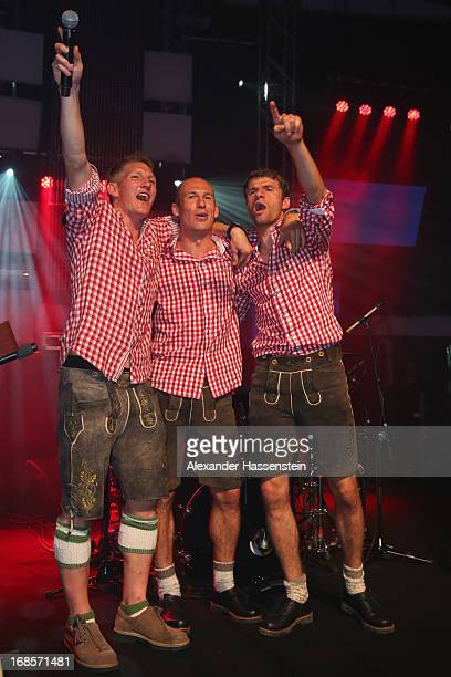 Bastian Schweinsteiger of Bayern Muenchen performes with his team mates Arjen Robben and Thomas Mueller live on stage during the Official Champion...