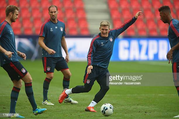 Bastian Schweinsteiger of Bayern Muenchen plays the ball with his team mates David Alaba Tom Starke and Jan Kirchhof during a training session prior...