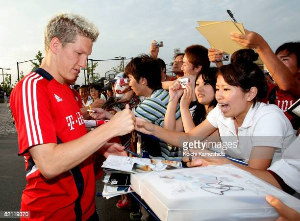 Bastian Schweinsteiger of Bayern Muenchen signs his autograph for Japanese fans during a practice session prior to the preseason match against Urawa...