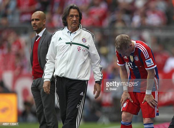 Bastian Schweinsteiger of Bayern Muenchen touches his leg after he was exchanged as team coach Josep Guardiola and team doctor HansWilhelm...