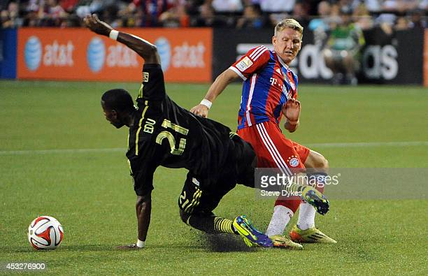 Bastian Schweinsteiger of Bayern Munich gets tangled up with Maurice Edu of the MLS AllStars duing the second half of the game at Providence Park on...