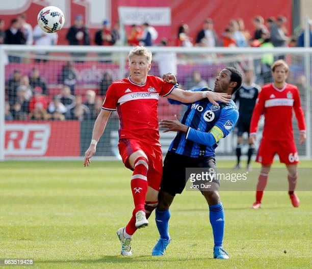 Bastian Schweinsteiger of Chicago Fire battles for the ball with Patrice Bernier of Montreal Impact during the first half at Toyota Park on April 1...