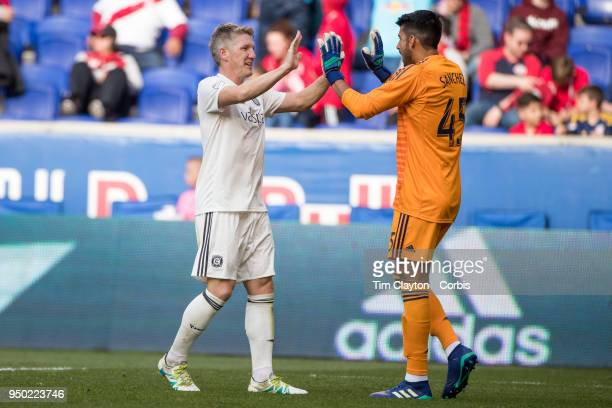Bastian Schweinsteiger of Chicago Fire celebrates with goalkeeper Richard Sanchez of Chicago Fire at the final whistle after his sides 21 win during...
