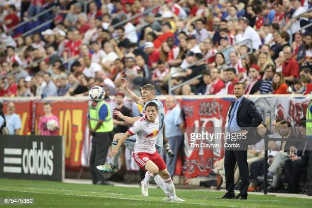 Bastian Schweinsteiger of Chicago Fire challenged by Connor Lade of New York Red Bulls as head coach Jesse Marsch of the New York Red Bulls looks on...