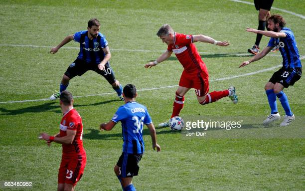 Bastian Schweinsteiger of Chicago Fire dribbles around Hernan Bernardello of Montreal Impact and Marco Donadel during the second half at Toyota Park...