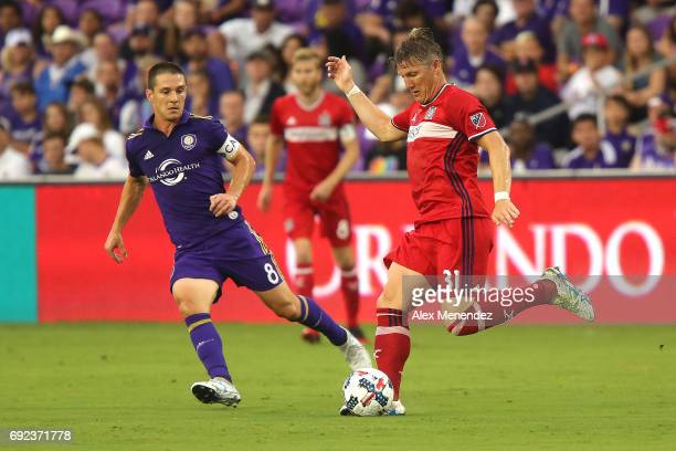 Bastian Schweinsteiger of Chicago Fire kicks the ball in front of Will Johnson of Orlando City SC during a MLS soccer match between the Chicago Fire...
