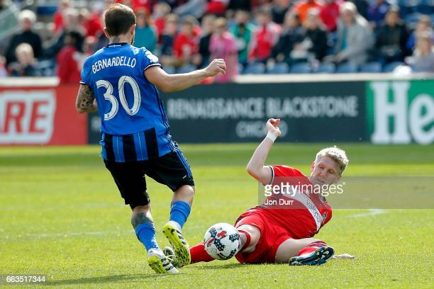 Bastian Schweinsteiger of Chicago Fire stoppage time against Hernan Bernardello of Montreal Impact during the second half at Toyota Park on April 1...