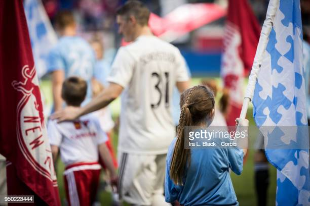 Bastian Schweinsteiger of Chicago Fire walks onto the field through the Autism Awareness Flag and the Red Bulls Flag during the Major League Soccer...