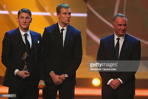 Bastian Schweinsteiger of FC Bayern Muenchen his team mate Holger Badstuber and CEO of Bayern Muenchen KarlHeinz Rummenigge receives the Team of the...