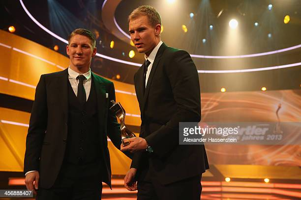 Bastian Schweinsteiger of FC Bayern Muenchen holds with his team mate Holger Badtsuber the Team of the Year 2013 award after the Sportler des Jahres...