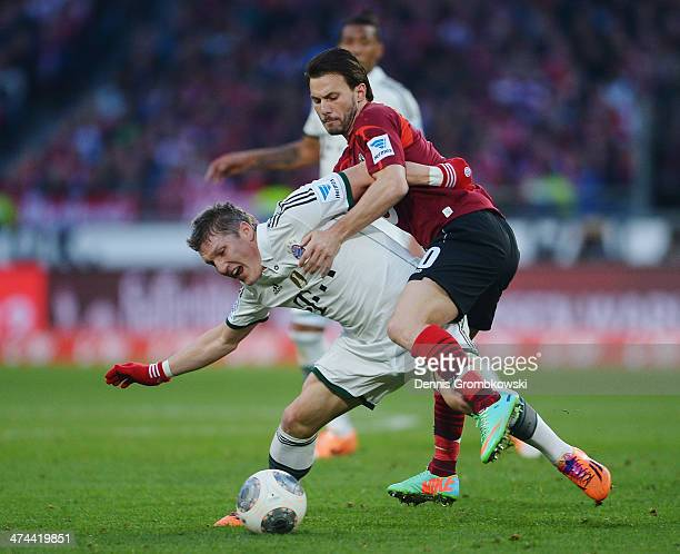 Bastian Schweinsteiger of FC Bayern Muenchen is challenged by Szabolcs Huszti of Hannover 96 during the Bundesliga match between Hannover 96 and FC...