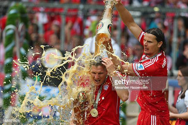 Bastian Schweinsteiger of FC Bayern Muenchen is drenched in beer by teammate Daniel van Buyten following their match against Augsburg at the Allianz...