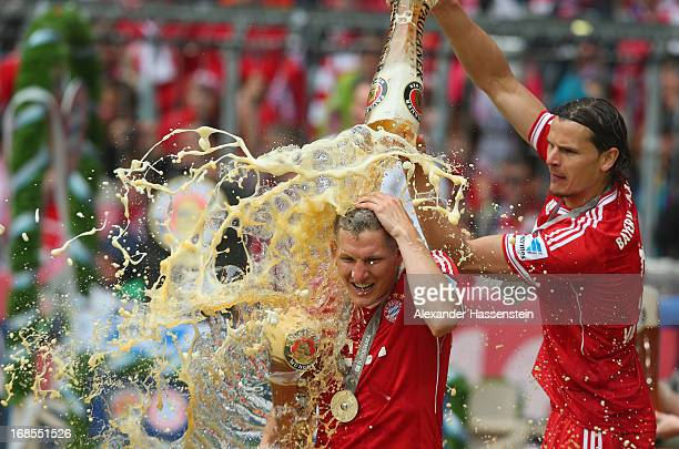 Bastian Schweinsteiger of FC Bayern Muenchen is drenched in beer by team-mate Daniel van Buyten following their match against Augsburg at the Allianz...