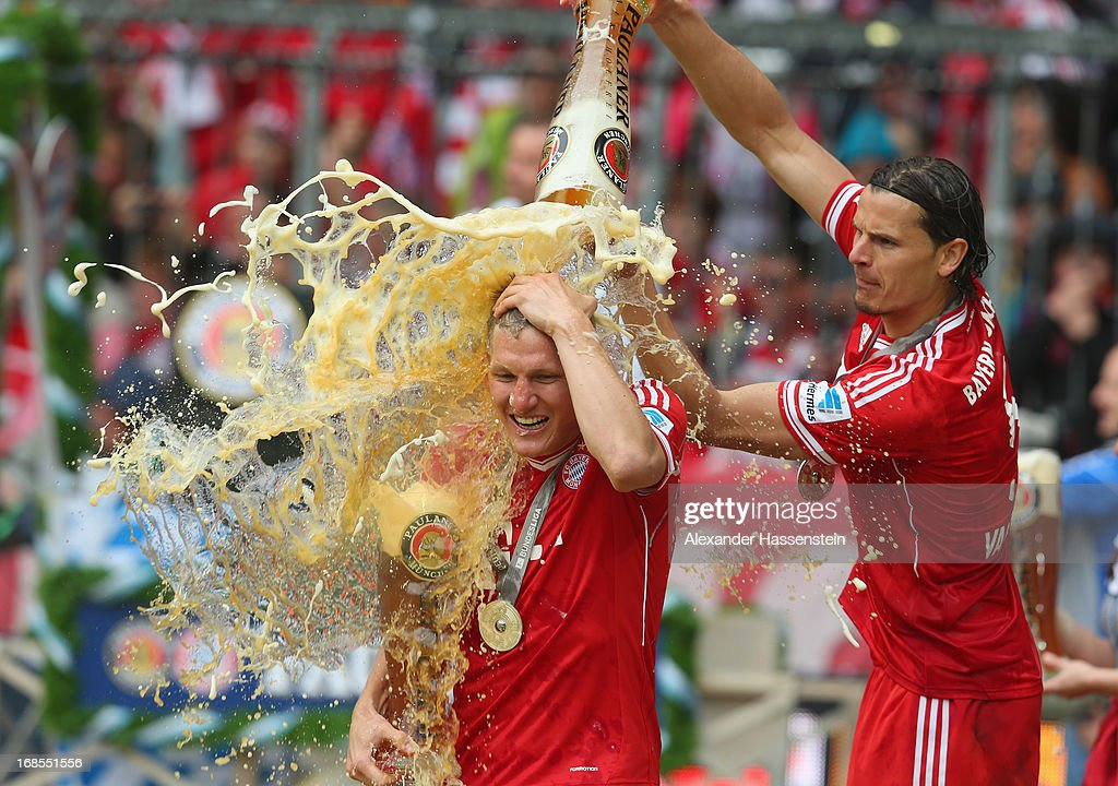 Bastian Schweinsteiger of FC Bayern Muenchen is drenched in beer by team-mate Daniel van Buyten following their match against Augsburg at the Allianz Arena on May 11, 2013 in Munich, Germany.