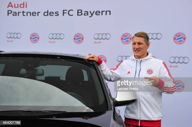 Bastian Schweinsteiger of FC Bayern Muenchen poses with his car during the car handover of Audi on August 23 2014 in Neuburg an der Donau Germany