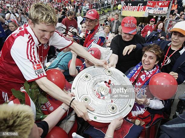 Bastian Schweinsteiger of FC Bayern Munich presents the trophy to handicapped fans after the Bundesliga match between FC Bayern Munich and 1 FC...