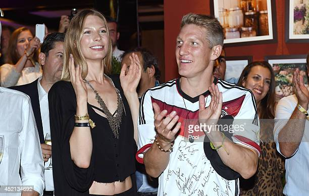 Bastian Schweinsteiger of Germany and girlfriend Sarah Brandner celebrate with teammates at a party after winning the 2014 FIFA World Cup Brazil...