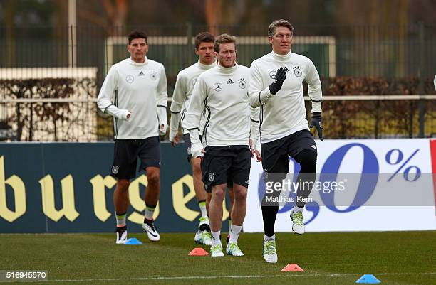 Bastian Schweinsteiger of Germany and his team mates look on during a Germany training session ahead of their International frindly match against...