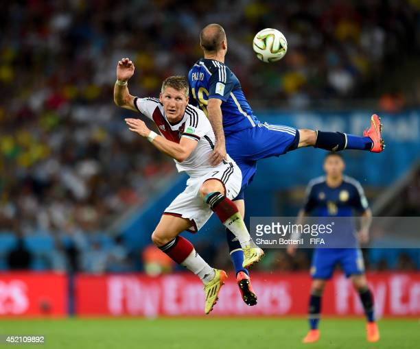 Bastian Schweinsteiger of Germany and Rodrigo Palacio of Argentina compete for the ball during the 2014 FIFA World Cup Brazil Final match between...