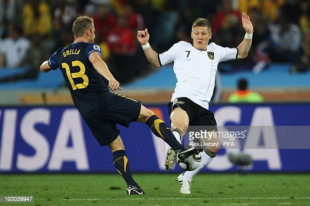 Bastian Schweinsteiger of Germany and Vince Grella of Australia battle for the ball during the 2010 FIFA World Cup South Africa Group D match between...