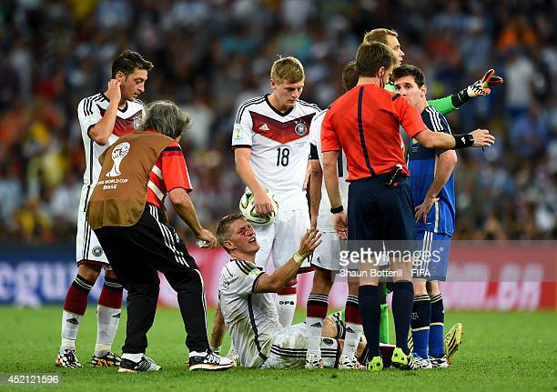 Bastian Schweinsteiger of Germany appeals to referee Nicola Rizzoli as he bleeds after a clash during the 2014 FIFA World Cup Brazil Final match...