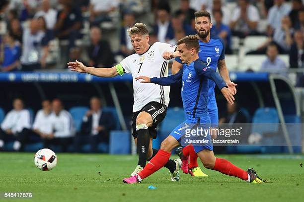 Bastian Schweinsteiger of Germany battles for the ball with Antoine Griezmann during the UEFA EURO semi final match between Germany and France at...
