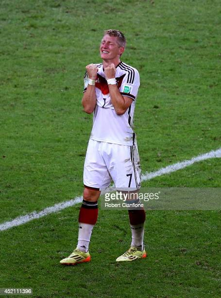 Bastian Schweinsteiger of Germany celebrates after defeating Argentina 10 in extra time during the 2014 FIFA World Cup Brazil Final match between...
