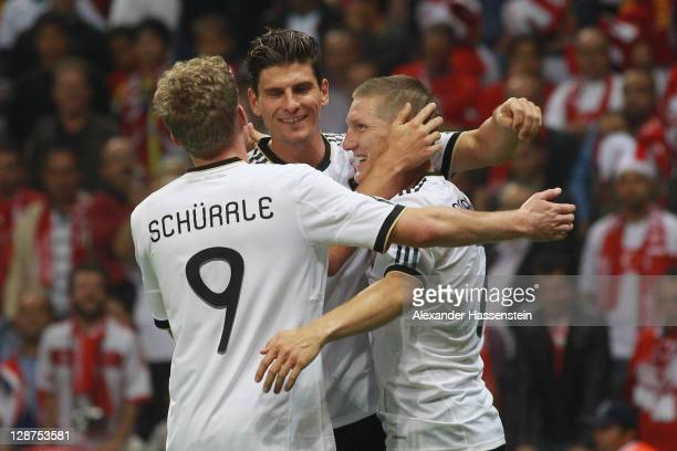 Bastian Schweinsteiger of Germany celebrates scoring the 3rd goal with his team mates Mario Gomez and Andre Schuerrle during the UEFA EURO 2012 Group...
