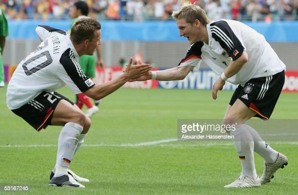 Bastian Schweinsteiger of Germany celebrates scoring the 3rd goal with team mate Lukas Podolski of Germany during the match between Germany and...