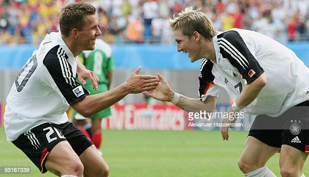 Bastian Schweinsteiger of Germany celebrates scoring the 3rd goal with team mate Lukas Podolski of Germany during the match between Germany and...