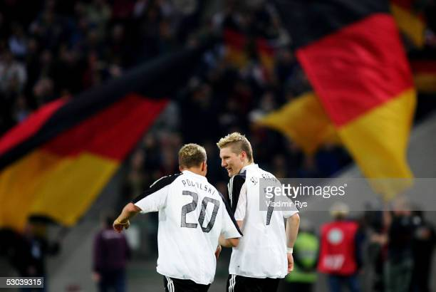 Bastian Schweinsteiger of Germany chats with teammate Lukas Podolski after scoring his second goal during the friendly match between Germany and...
