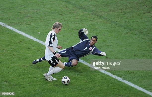 Bastian Schweinsteiger of Germany dodges goalkeeper Ali Boumnijel of Tunisia to score the second goal during The FIFA Confederations Cup Match...