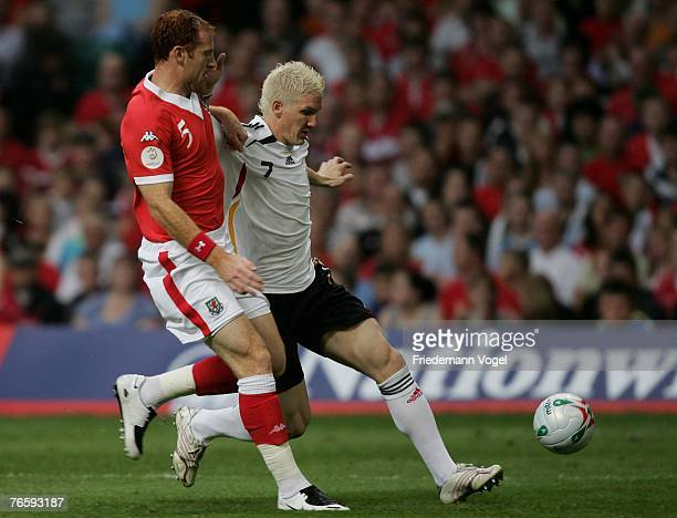 Bastian Schweinsteiger of Germany fights for the ball with James Collins of Wales during the Euro 2008 qualifying match between Wales and Germany at...