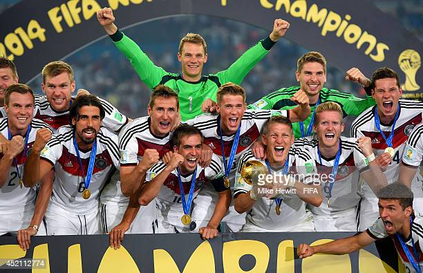 Bastian Schweinsteiger of Germany holds the World Cup while posing for photographs with his teammates after the 2014 FIFA World Cup Brazil Final...