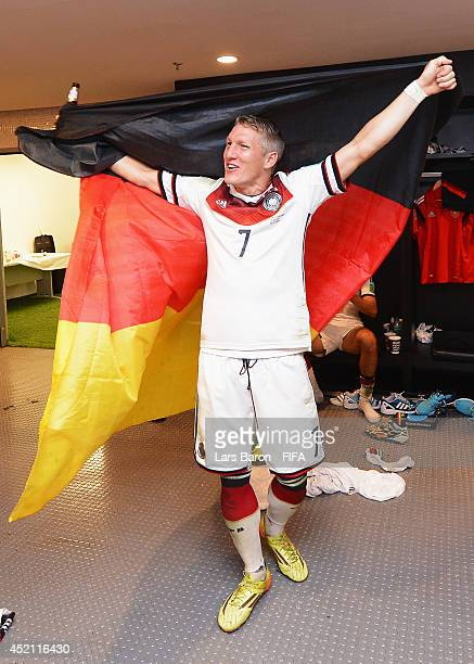Bastian Schweinsteiger of Germany holds up a German flag in the Germany dressing room after the 2014 FIFA World Cup Brazil Final match between...