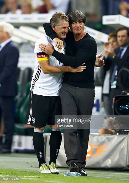 Bastian Schweinsteiger of Germany hugs Joachim Loew coach of Germany after being substituted during the International Friendly match between Germany...