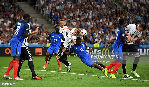 Bastian Schweinsteiger of Germany is challenged by Paul Pogba of France in the penalty area during the UEFA EURO semi final match between Germany and...