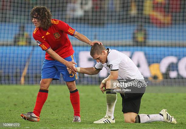 Bastian Schweinsteiger of Germany is consoled by goalscorer Carles Puyol of Spain after being knocked out of the competition during the 2010 FIFA...
