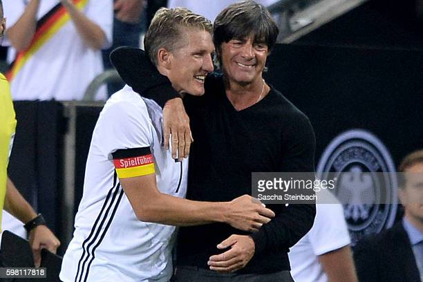 Bastian Schweinsteiger of Germany is huged by head coach Joachim Loew after his substitution during the international friendly match between Germany...