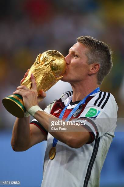 Bastian Schweinsteiger of Germany kisses the World Cup trophy after defeating Argentina 10 in extra time during the 2014 FIFA World Cup Brazil Final...