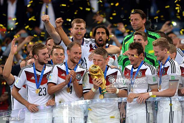Bastian Schweinsteiger of Germany kisses the World Cup trophy to celebrate with his teammates during the award ceremony after the 2014 FIFA World Cup...