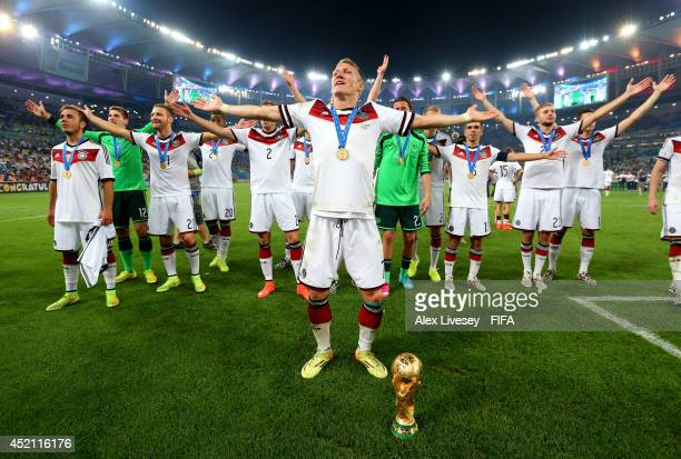 Bastian Schweinsteiger of Germany leads team-mates in celebration after the 2014 FIFA World Cup Brazil Final match between Germany and Argentina at...