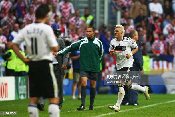 Bastian Schweinsteiger of Germany leaves the pitch after been booked with a red card and sent off by referee Frank De Bleeckere of Belgium during the...