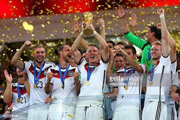 Bastian Schweinsteiger of Germany lifts the World Cup trophy to celebrate with his teammates during the award ceremony after the 2014 FIFA World Cup...